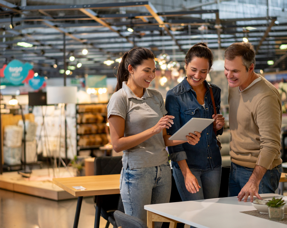 Cheerful sales woman showing a design on tablet to mid adult couple looking for furniture at a home store